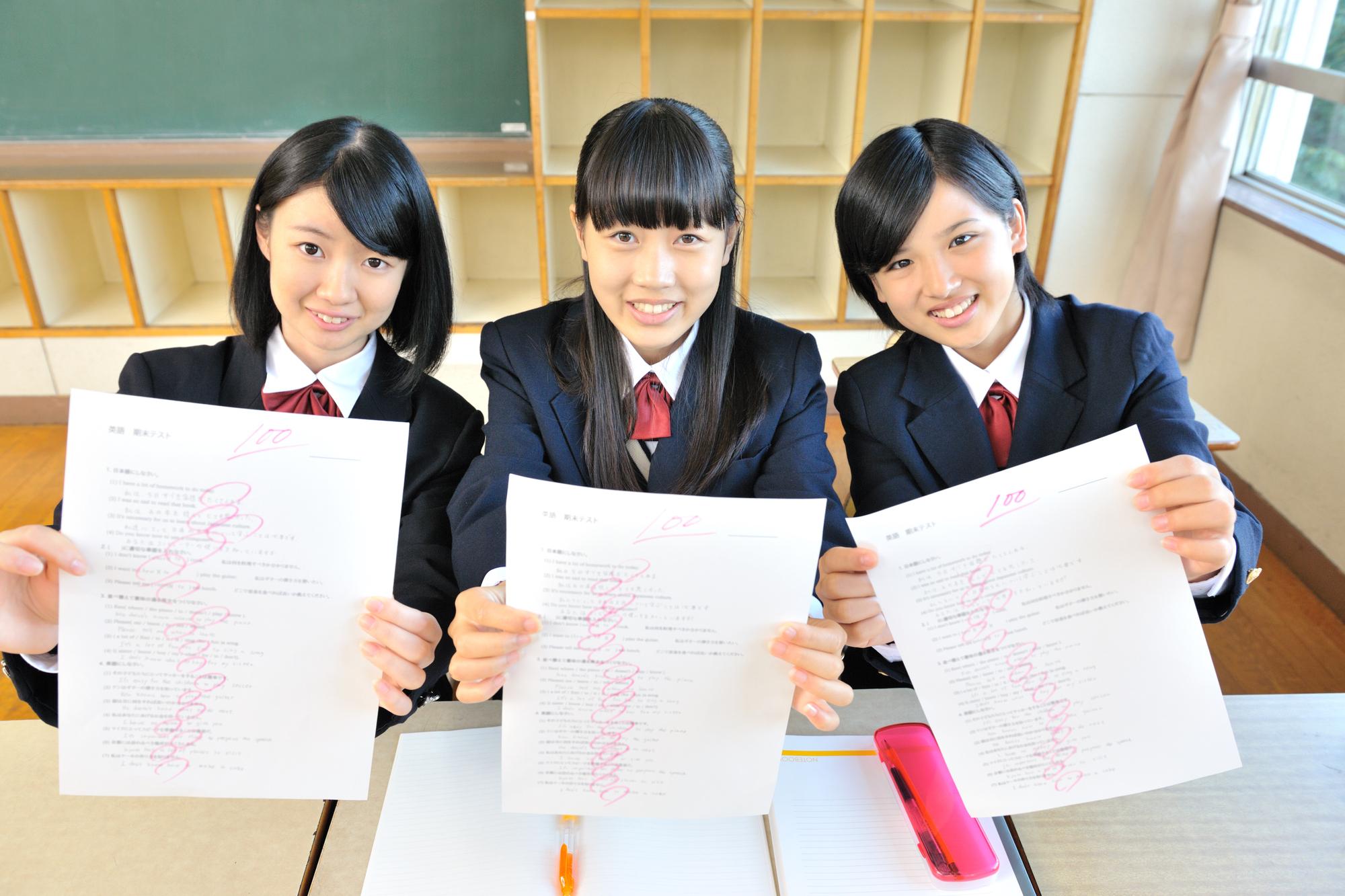100点の答案を掲げる女子中学生トリオ