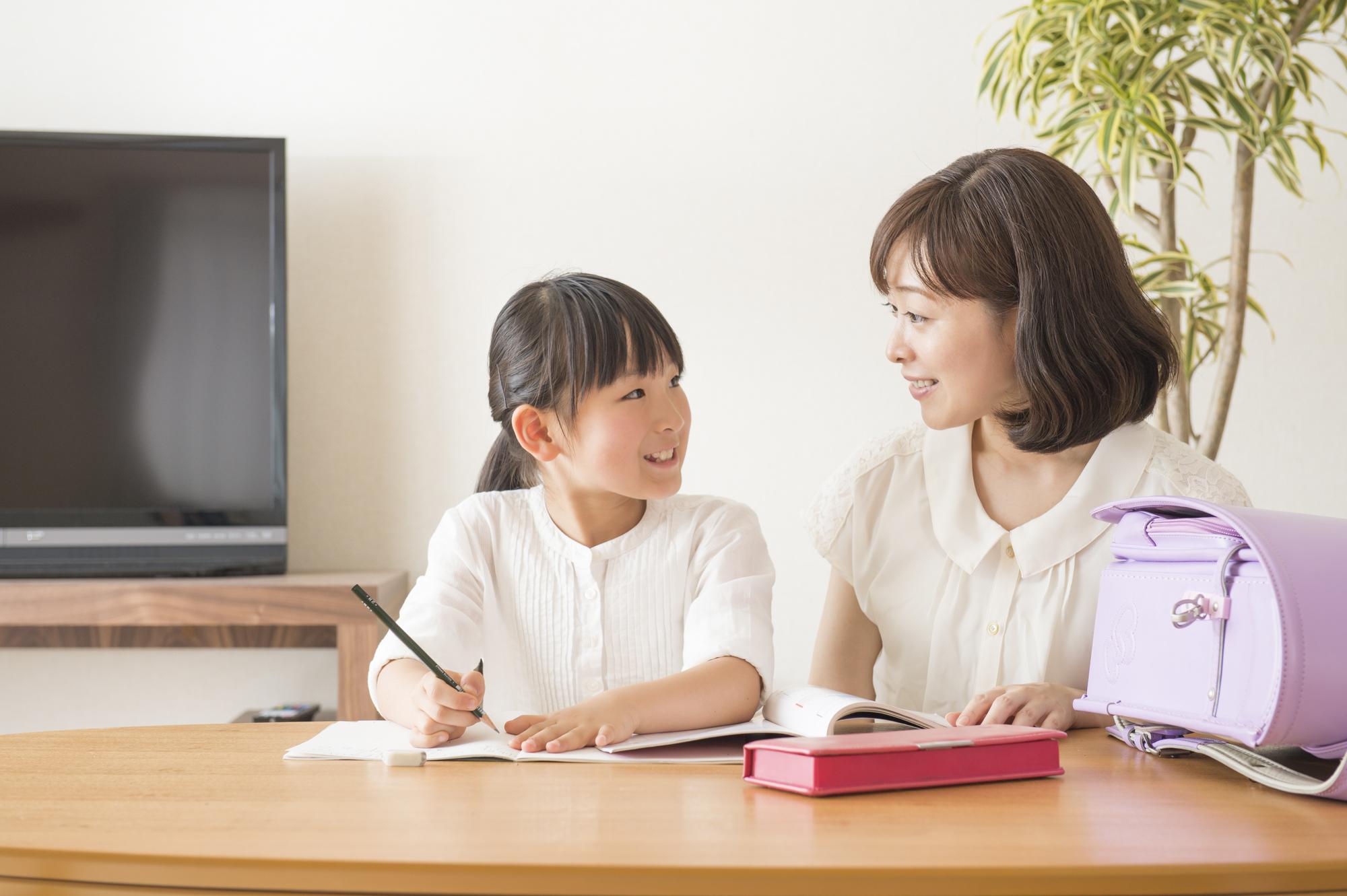 宿題する娘を褒める母親