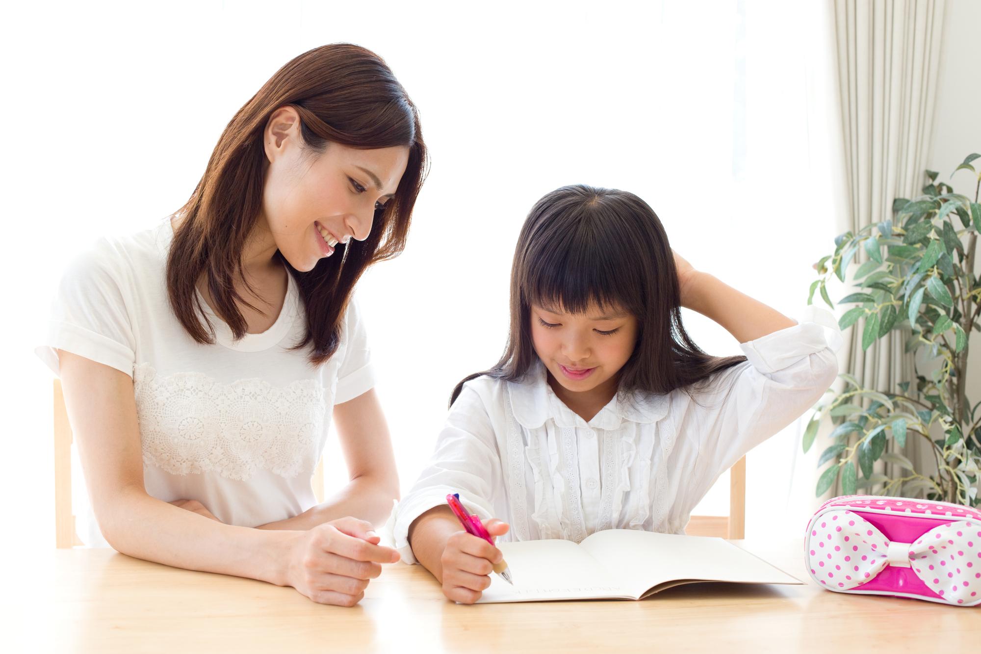 勉強する娘を励ます母親
