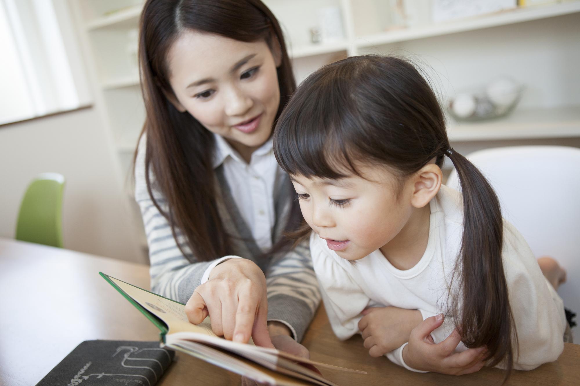 絵本を眺める女の子と母親