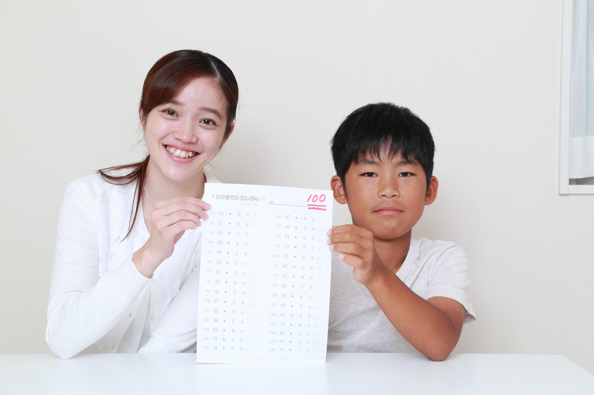 100点の答案を掲げる母と息子