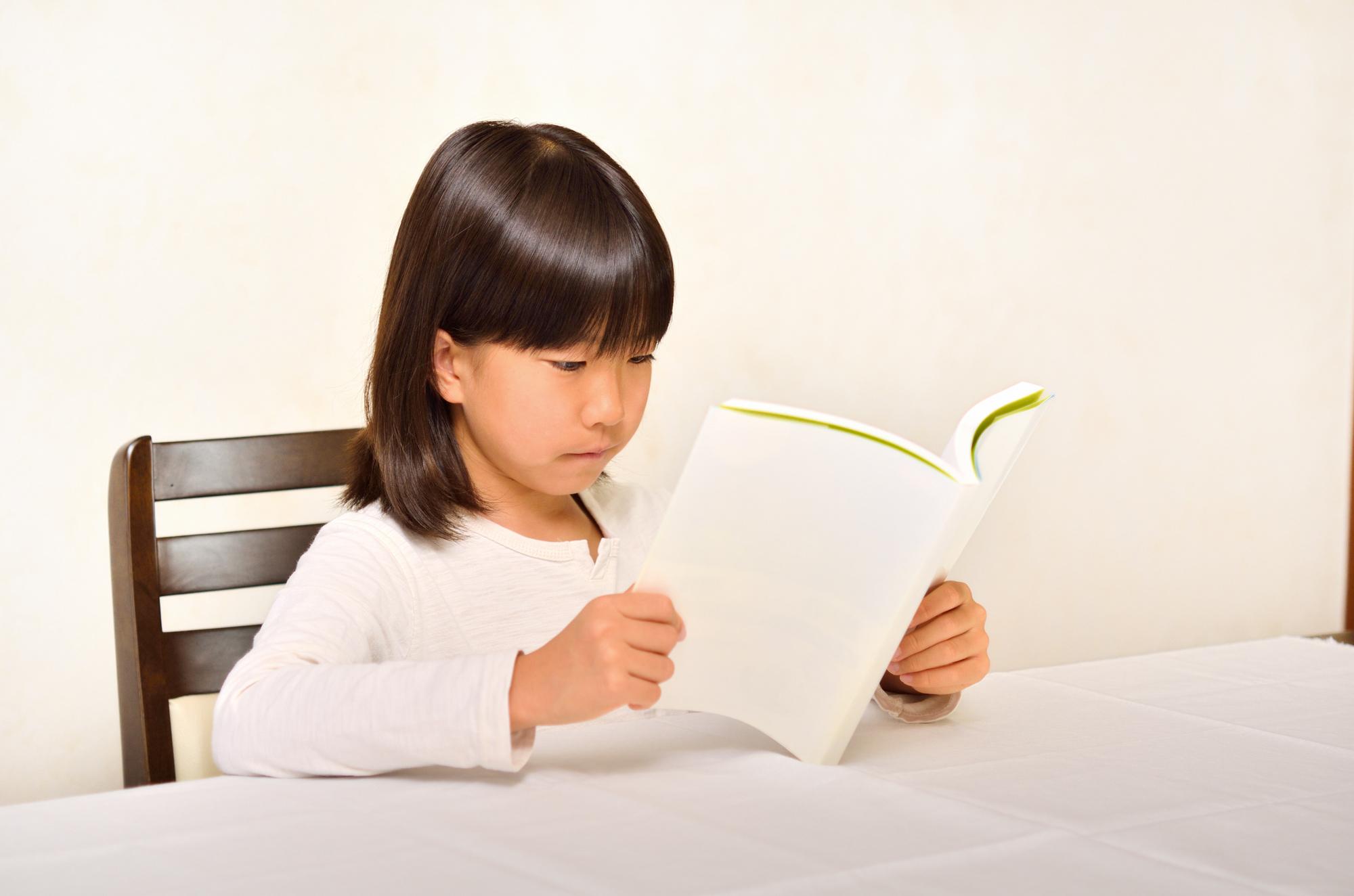 テーブルで本を読む白い服の女の子