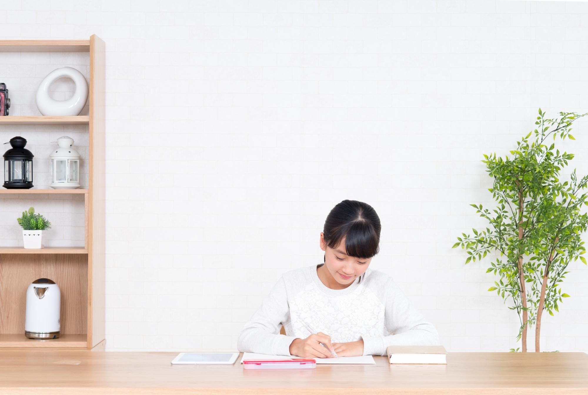 本とノートを使って勉強する白い服の女の子