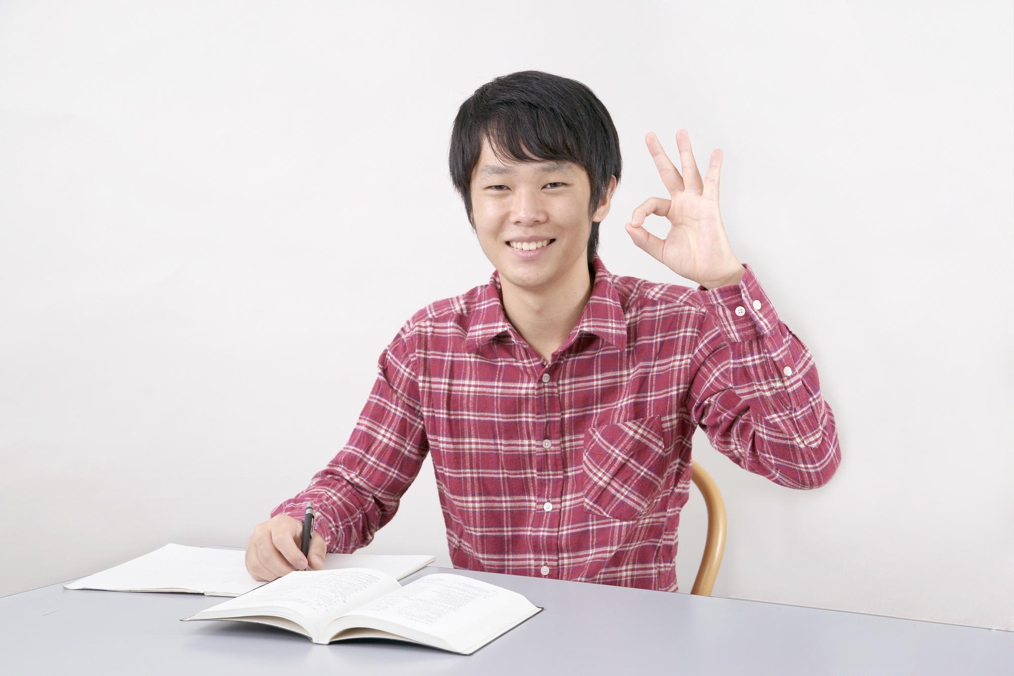 指でOKサインをする男子中学生