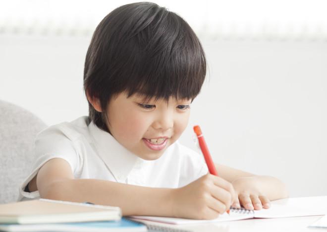 赤いペンで勉強する男の子