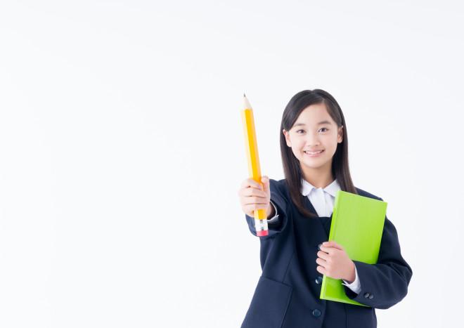 大きな鉛筆をかざす女子中学生