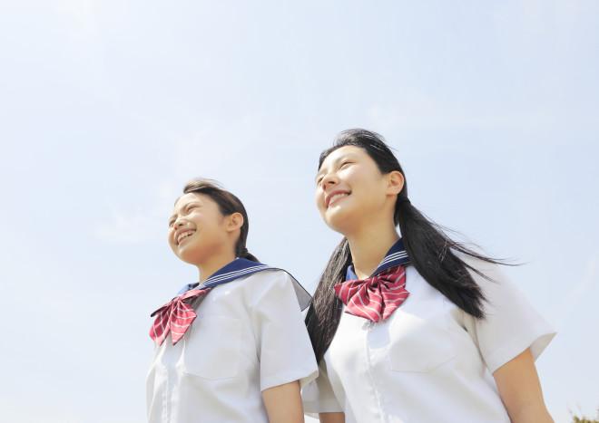 青空の下に立つ女子中学生2人