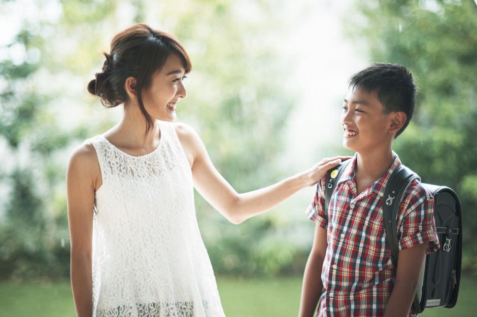 男の子と、その肩に手を置く母親