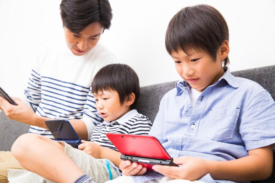 ゲームをする息子2人とお父さん